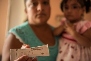 Woman and her child holding the treatement for Chagas